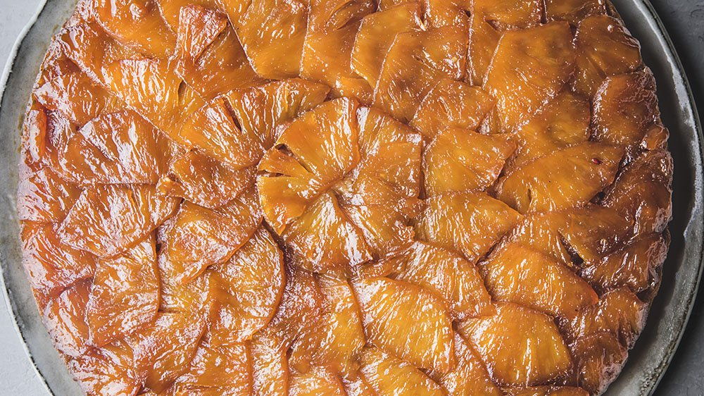Haitian Pineapple Upside Down Cake recipe From the book EVERYONE'S TABLE by Gregory Gourdet and JJ Goode. Copyright © 2021 by Gregory Gourdet and JJ Goode. Published by Harper Wave, an imprint of HarperCollins Publishers. Reprinted by permission. Photos by Eva Kosmas Flores.